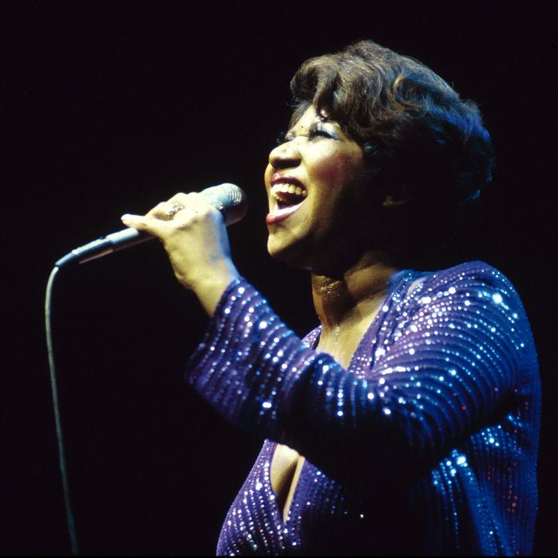 Aretha Franklin singing on stage in a blue dress