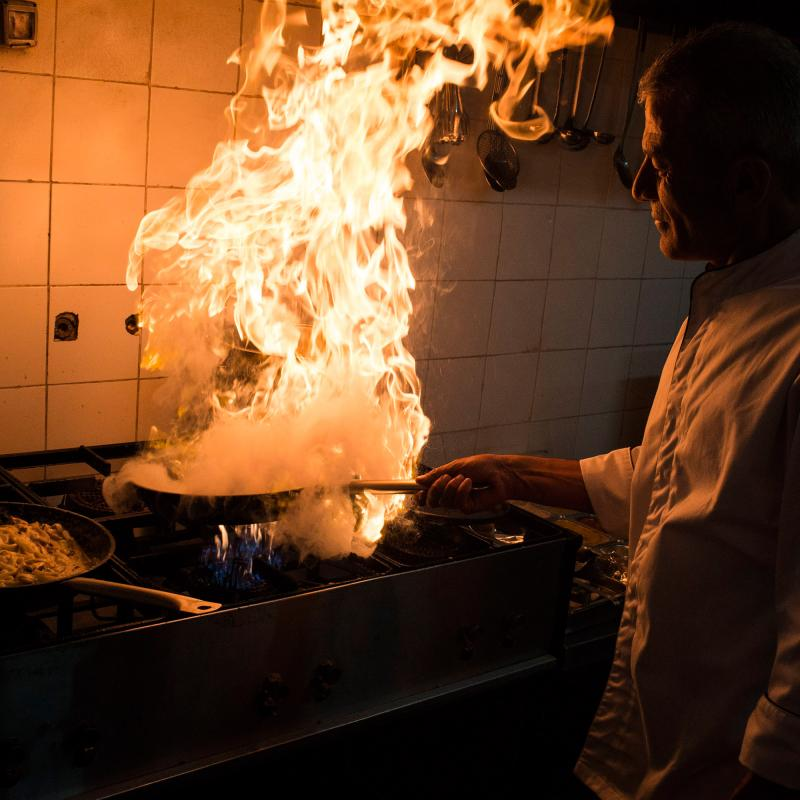 A Palestinian chef cooking with a large fire on a stovetop