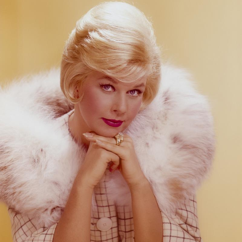 Doris Day resting her head on her hands against a yellow backdrop