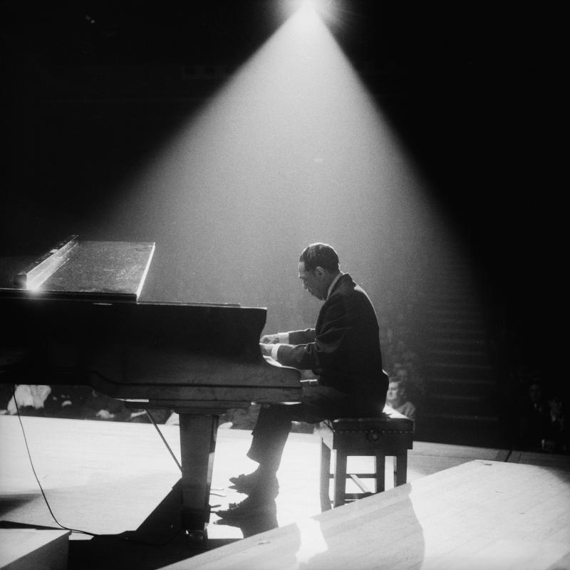 Jazz legend Duke Ellington playing the piano in a spotlight at a concert hall