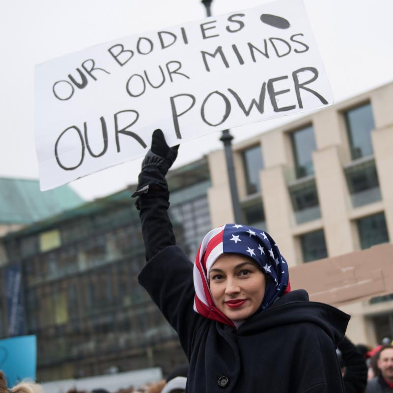 "Feminist demonstrator holds a sign that says ""Our bodies, our minds, our power"" while wearing an American flag headscarf"