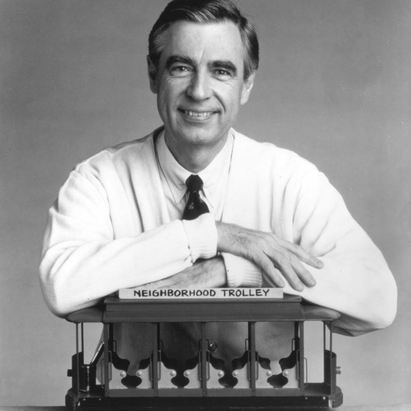 Fred Rogers, also known as Mister Rogers, posing with the Neighborhood Trolly from his show Mister Rogers Neighborhood