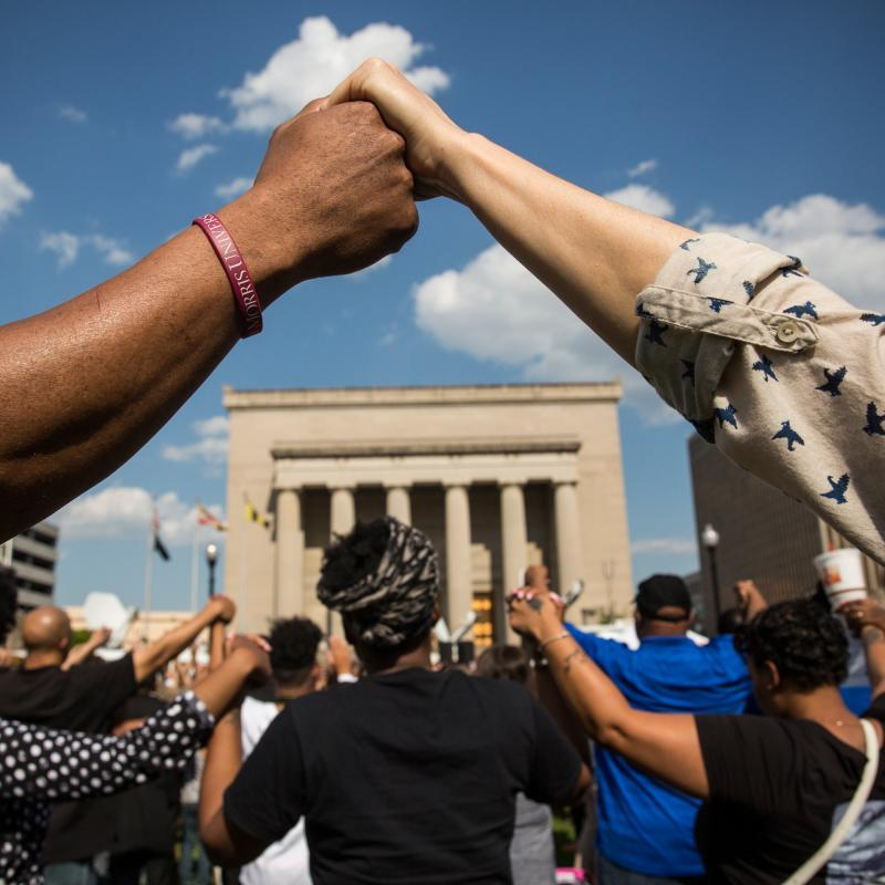 People holding hands at a rally