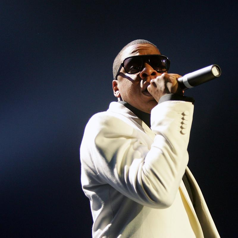Rapper Jay-Z holding a mic and performing on stage in a white suit
