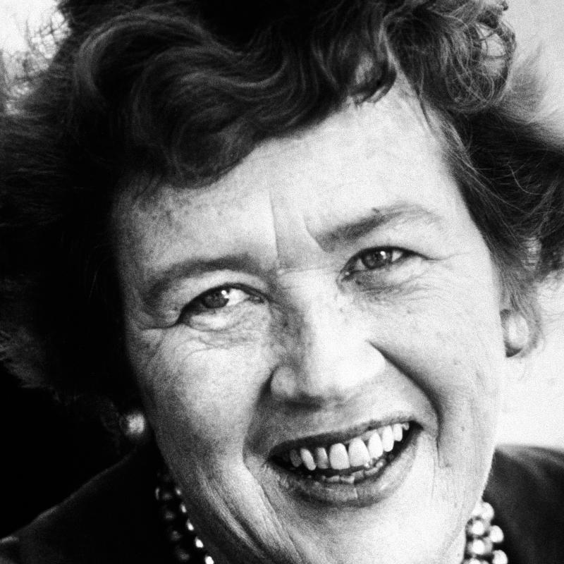 Portrait of chef and author Julia Child smiling in an old black and white photo