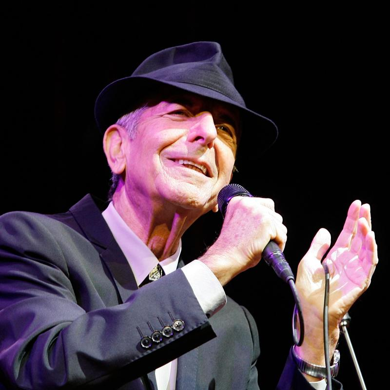 Musician Leonard Cohen singing on stage in a black suit and hat