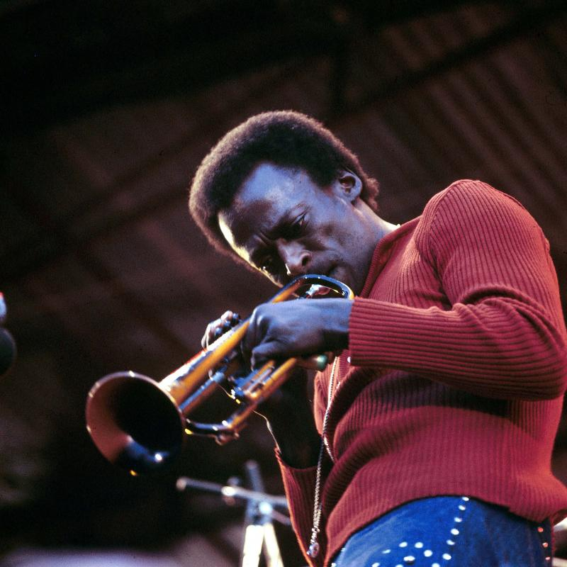 Jazz legend Miles Davis playing the trumpet in a red shirt