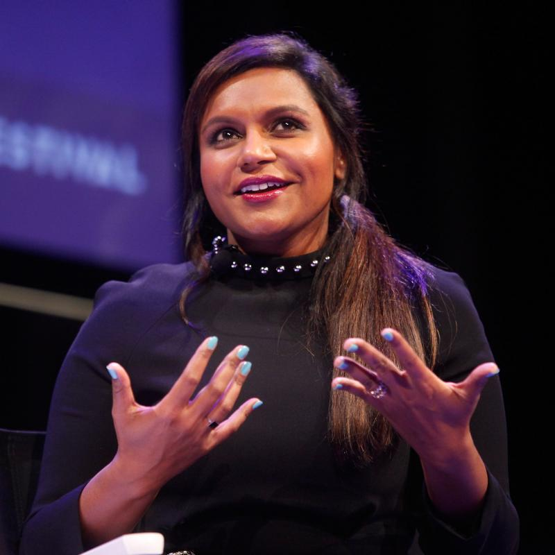 Mindy Kaling speaking on stage in a black top