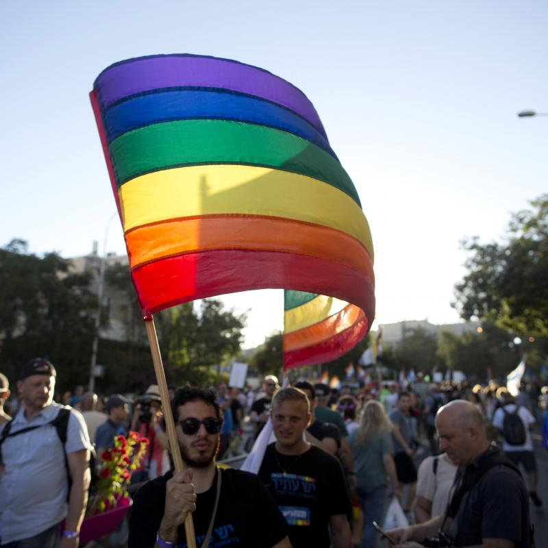 Israeli pride parade with a man waving the rainbow flag