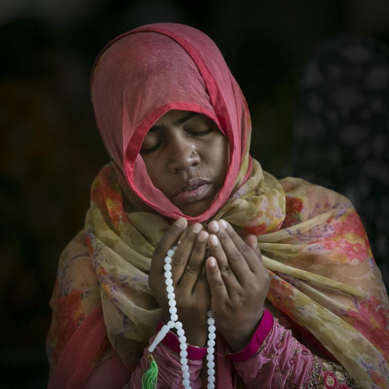 A Muslim girl praying with beads in a colorful headscarf