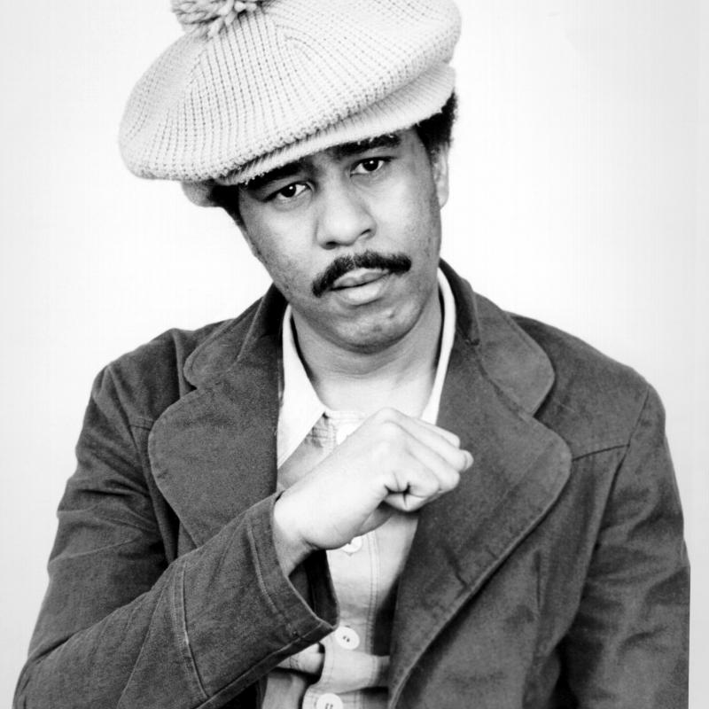 Comedian Richard Pryor making a fist and wearing a hat