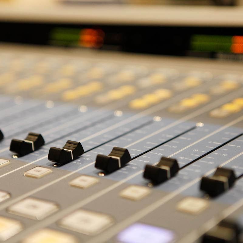 Close-up view of a music studio mixing board