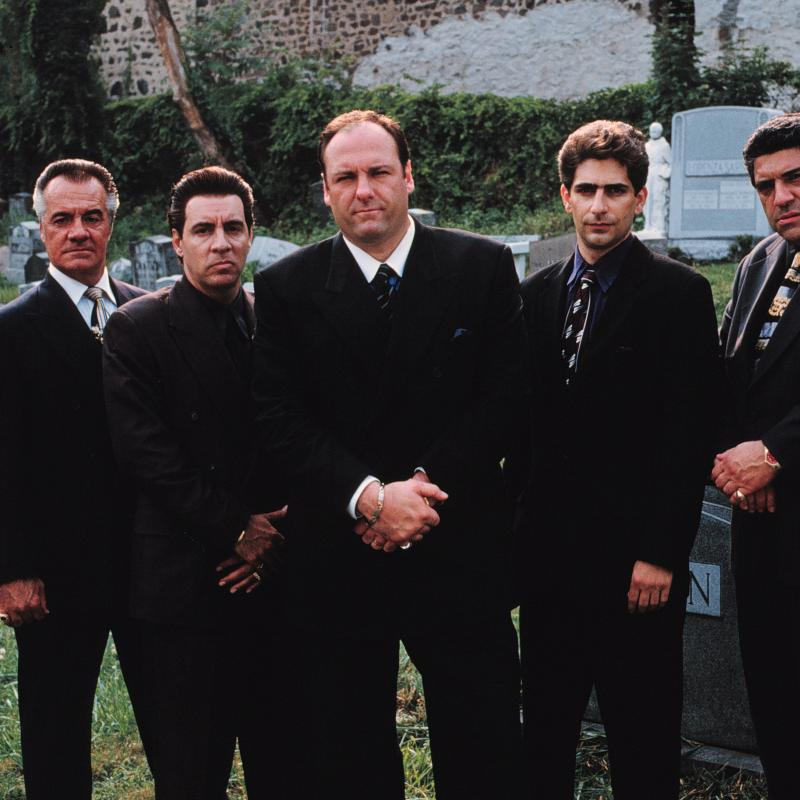 James Gandolfini, as Tony Soprano, standing in a cemetery surrounded by his Sopranos cast stars in a still image from an episode of the HBO show The Sopranos