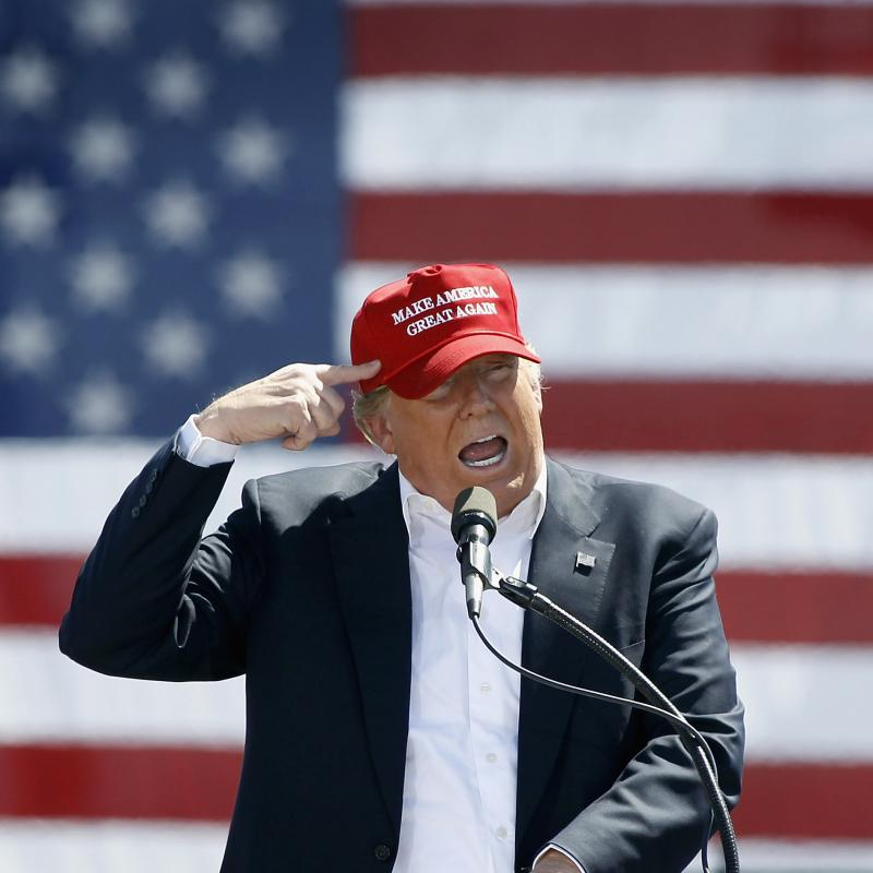 Donald Trump speaking at a campaign event in a MAGA hat with an American flag backdrop
