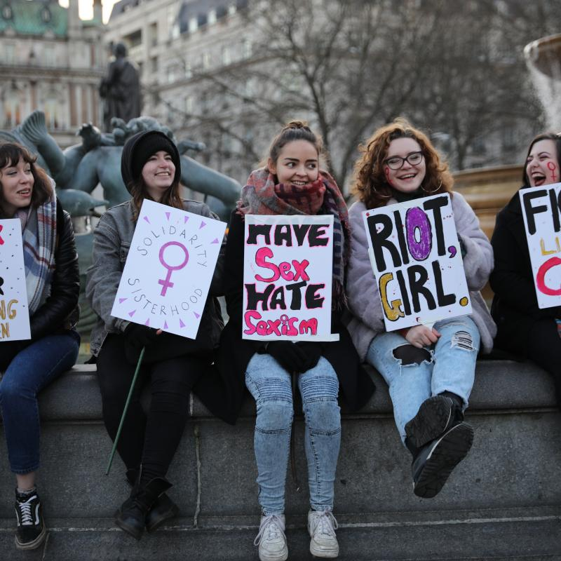 A group of young feminist girls holding protest signs at a demonstration