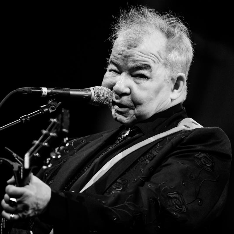 John Prine plays his guitar and looks at the camera during a live performance
