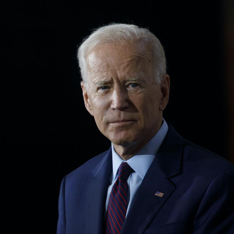 Joe Biden looks away from the camera in a dark suit against a black background