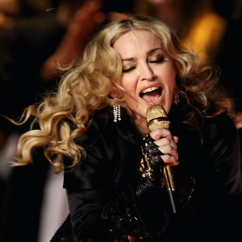 Madonna sings into a golden microphone during the Super Bowl halftime show