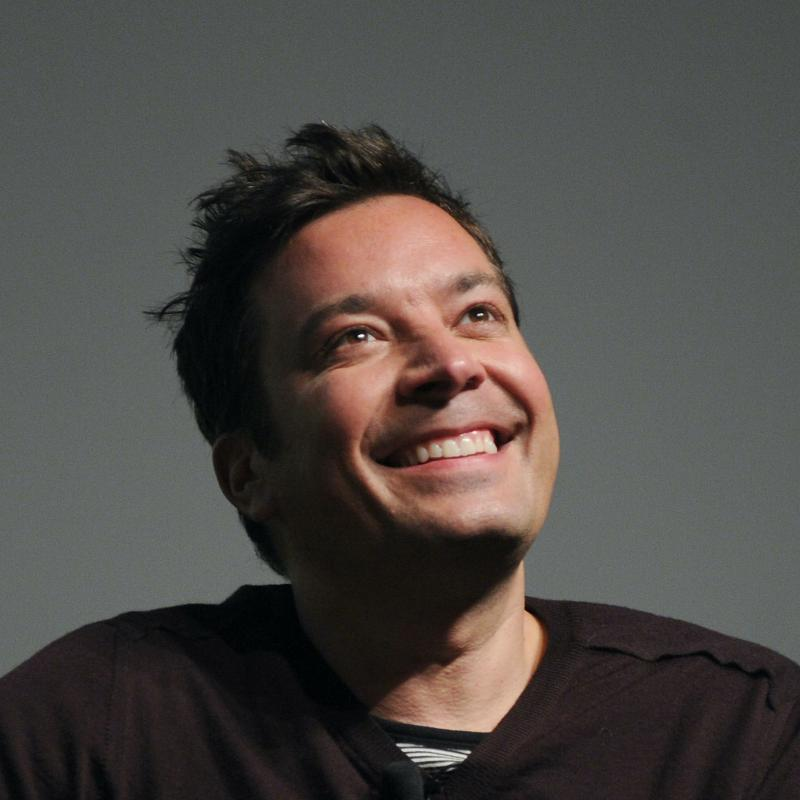 Comedian and talk show host Jimmy Fallon smiles and looks upwards against a gray background