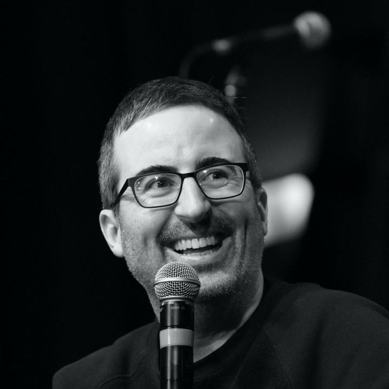 Comedian John Oliver laughs in front of a microphone in black and white.
