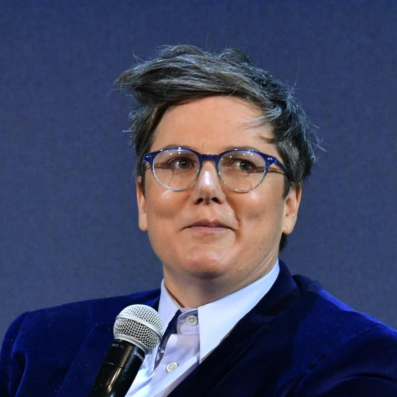 Comedian Hannah Gadsby smirks while holding a mic