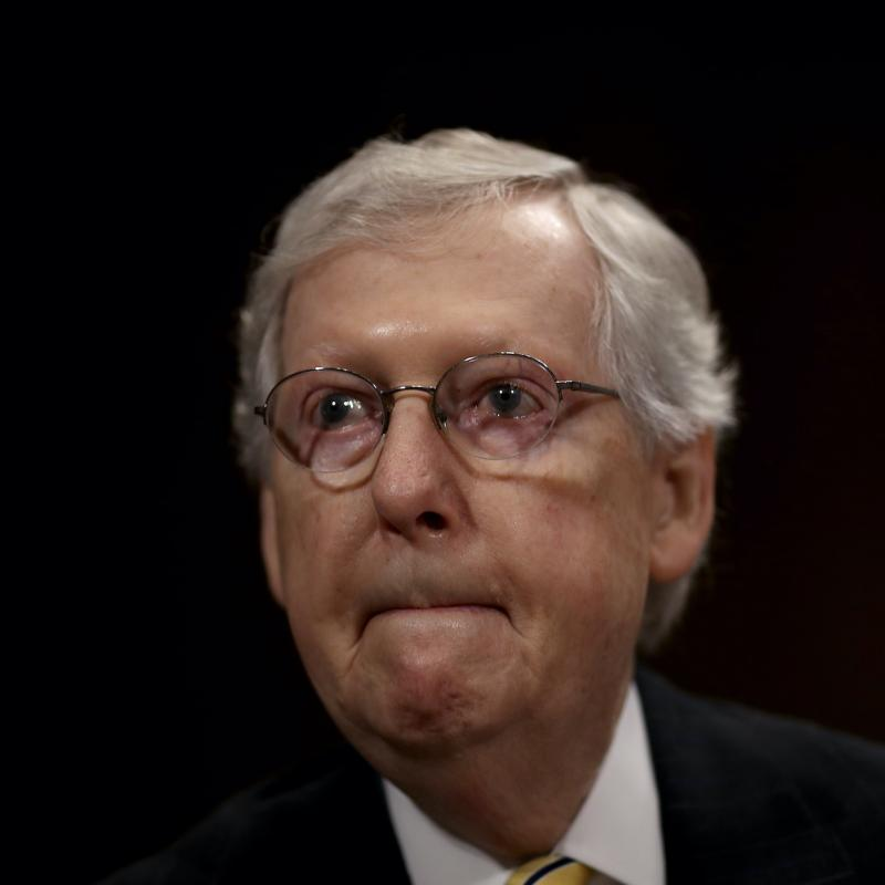 Senate Majority Leader Mitch McConnell looks pensive against a black backdrop