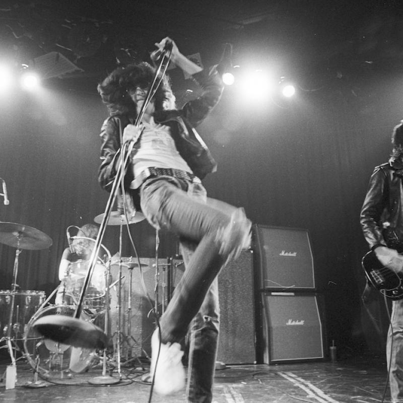 Joey Ramone performing on stage with his band The Ramones