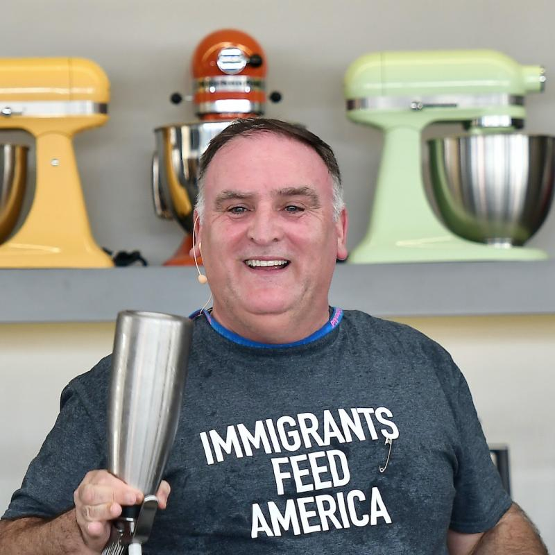 "Chef Jose Andres stands at a table full of kitchen equipment wearing a shirt that says ""Immigrants Feed America"""